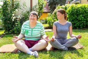 A woman doing yoga with her disability support worker sitting next to her