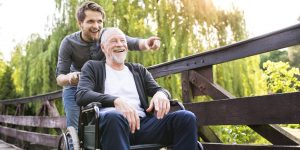 An eldery man in a wheelchair being pushed by a support worker and both smiling